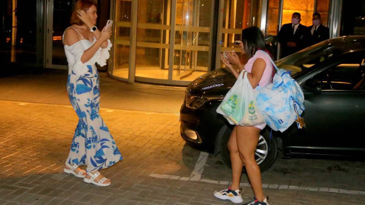 Flay chega ao hotel de máscara e posa com fãs