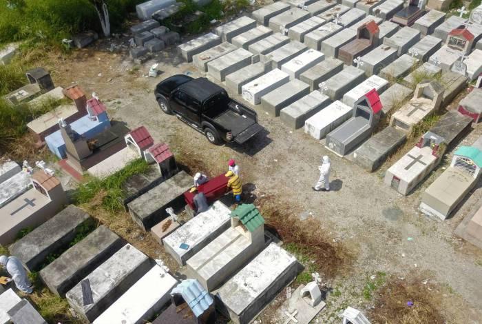 Trabalhadores enterram um caixão no cemitério Maria Canals, nos arredores de Guayaquil, Equador, em 12 de abril de 2020, em meio ao novo surto de coronavírus