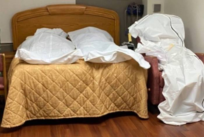 Dois cadáveres, vítimas de covid-19, deitados em um quarto de hospital