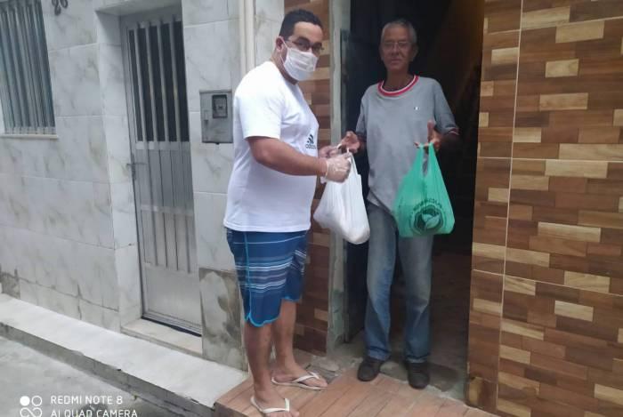 Diego Henrique retira doação na porta da casa de Celson Morais, de 58 anos, em São Cristóvão