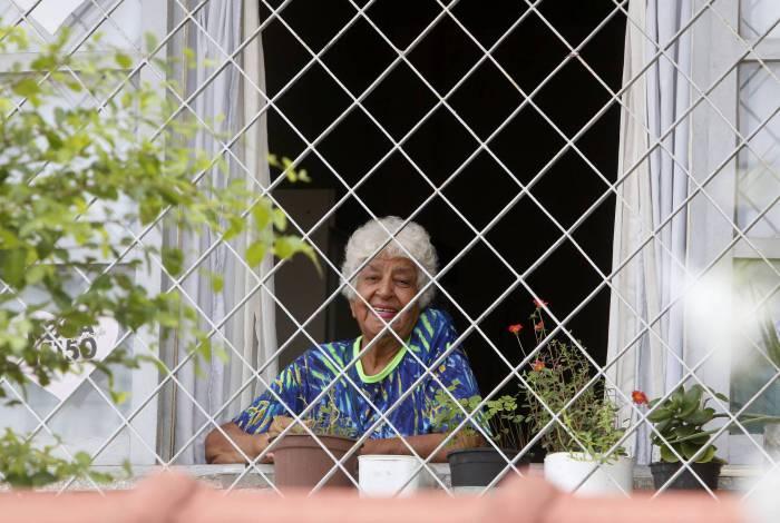 Rio de Janeiro - RJ  - 16/04/2020 - COVID 19 - Coronavirus na cidade do Rio - Na foto, Senhora em isolamento social, observa da janela de casa o movimentaçao na rua, proximo a Praça do Chafariz, em Madureira, zona norte do Rio - Foto Reginaldo Pimenta / Agencia O Dia