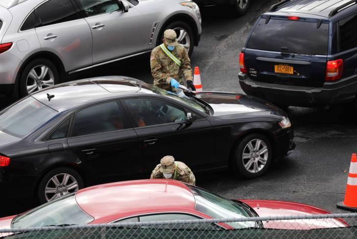 Membros da Guarda Nacional do Exército trabalham em local de testes de coronavírus aberto recentemente em 21 de abril de 2020 no bairro de Brooklyn, em Nova York