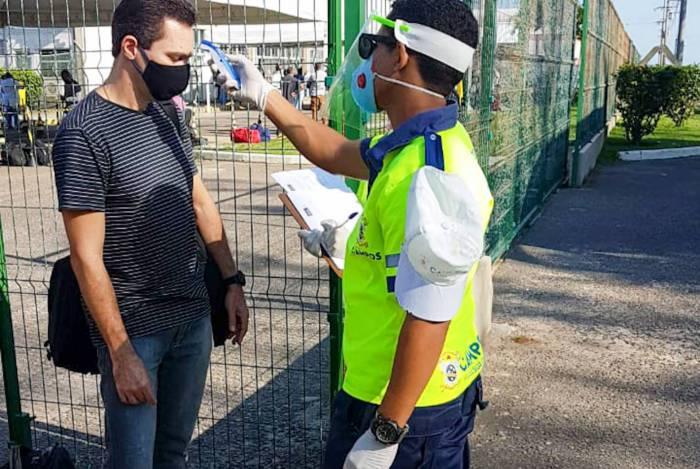 Trabalhadores embarcados da Petrobras passam por medição de temperatura em barreira sanitária montada pela prefeitura de Campos no heliporto do Farol