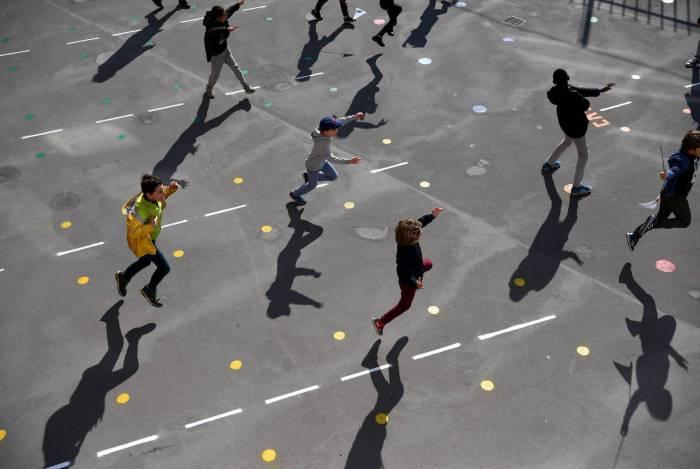 Alunos brincam no pátio da escola Saint Germain de Charonne, em Paris, em 14 de maio de 2020, depois que as escolas primárias na França reabriram esta semana
