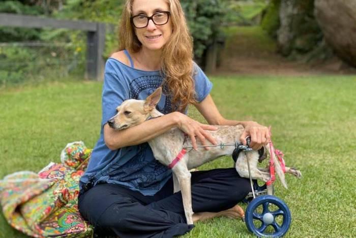 Betty Gofmann no sitio com Bebel, cachorra de rua paraplégica resgatada por ela