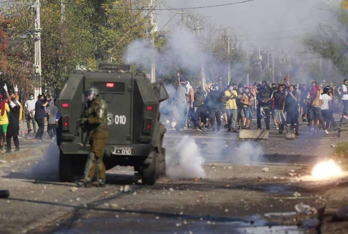 Manifestantes entram em conflito com a polícia de choque durante um protesto contra o governo do presidente chileno Sebastian Pinera em meio à pandemia do covid-19