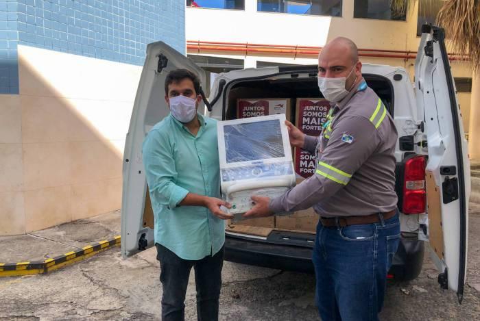 O prefeito de Campos, Rafael Diniz (à esquerda), recebe respiradores consertados de um funcionário do Porto do Açu