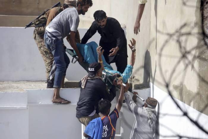 Voluntários carregam homem ferido após queda de avião comercial em área residencial perto do aeroporto de Karachi, no Paquistão