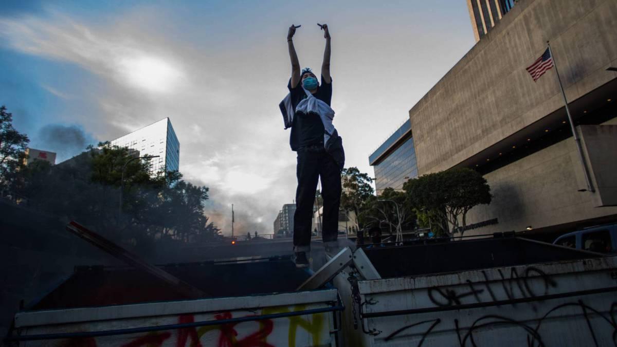 Um homem em cima de latas de lixo em chamas faz gestos contra a polícia no centro de Los Angeles