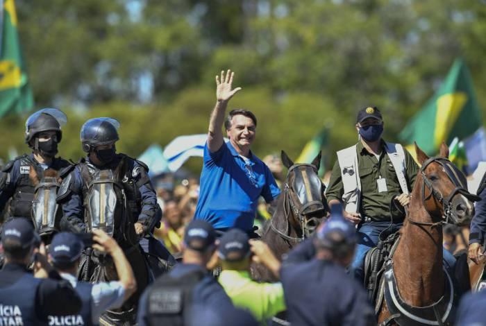 Montado em um cavalo da PM, Bolsonaro acena para manifestantes em frente ao Palácio do Planalto