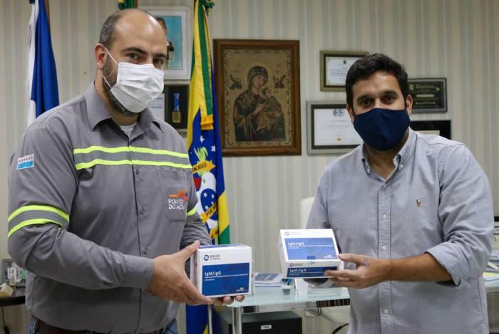 O prefeito de Campos, Rafael Diniz (à direita), recebe os testes de contaminação pela covid-19 de representante do Porto do Açu