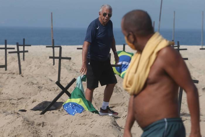 Um homem (de camisa) derrubou algumas das cruzes fincadas na areia da praia de Copacabana. Pai de vítima (sem camisa) as colocou de volta nos lugares e criticou postura