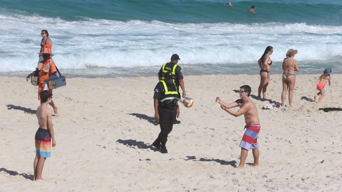 Policial tentar convencer as pessoas a saírem da areia