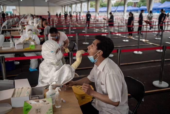 Profissional de saúde faz teste em um homem: 311 casos em Pequim