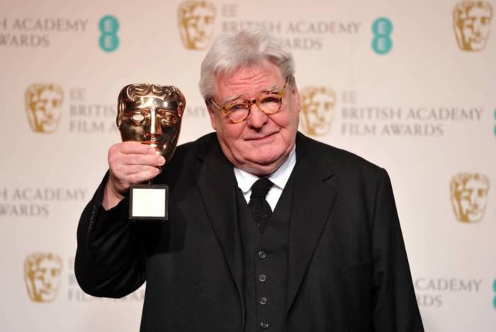 Alan Parker posa com seu prêmio BAFTA, em Londres