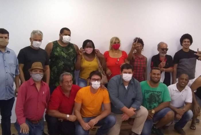 Luciano, abaixado, de camisa laranja. Do seu lado direito, o presidente do PT de Itaguaí, Marcos Garcia; do seu lado esquerdo, Marcus Skurti, presidente municipal do PCdoB