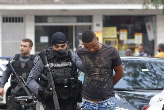Um dos suspeitos é conduzido pela polícia. Para ampliar território, a milícia passou a explorar transportes