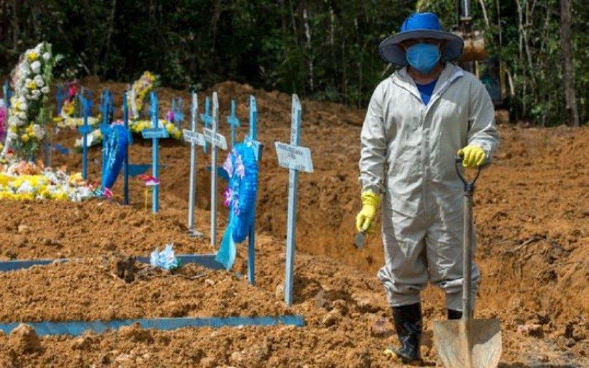 Coveiro com roupa impermeável em cemitério Nossa Senhora Aparecida, em Manaus. Nesta sexta (26), Brasil bateu mais um triste recorde: 3.650 pessoas morreram em 24 horas