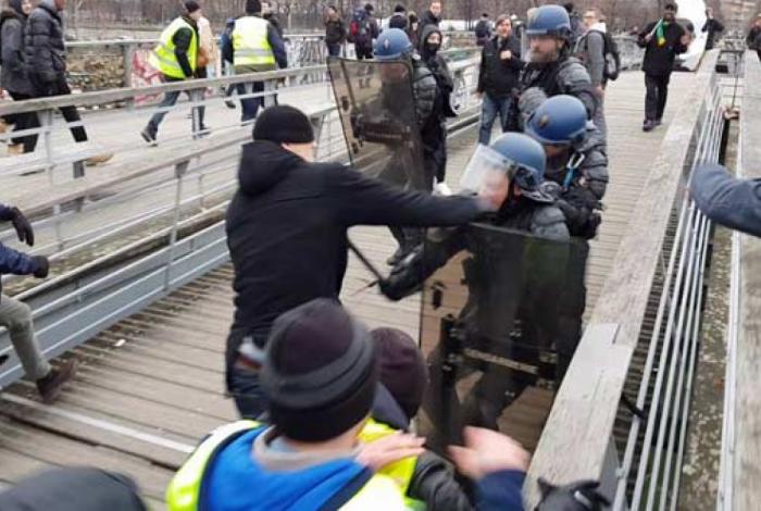 Cristophe Dettinger, ex-campeão nacional de peso-leve, foi filmado batendo em um policial durante uma manifestação perto do prédio do parlamento em Paris